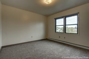 image of carpeted bedroom with two windows overlooking the neighborhood