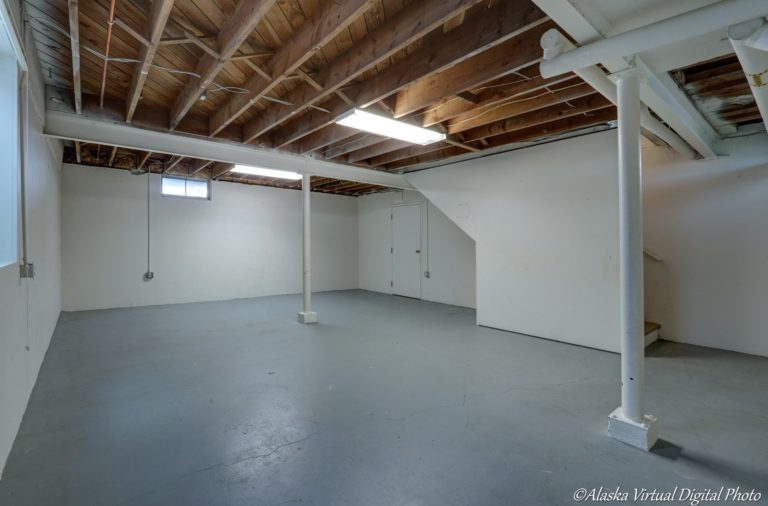 Unfinished basement with blue floor and exposed beams