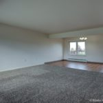 Carpeted living room with LVP dining room