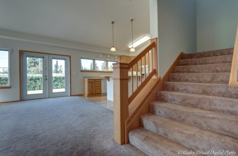 Stairway leading to upstairs on the right with large open living room with vaulted ceilings to the left