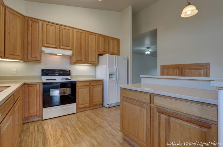 Kitchen with LVP flooring and light brown cabinets