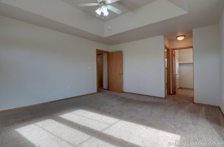 Large master bedroom with fan and raised ceiling