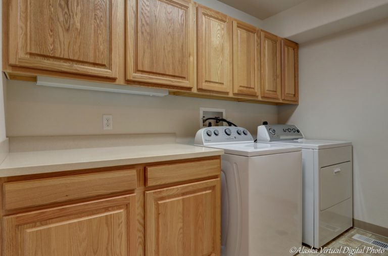 Laundry room with counters and multiple cabinets for storage
