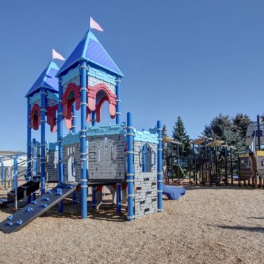 Blue, red & grey plastic playground castle with flags