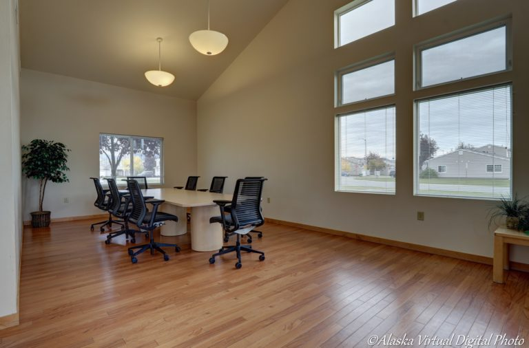 Business nook with wood floors, conference table and office chairs