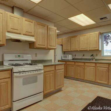 Image of kitchen with checked tile floors and light wooden cabinets
