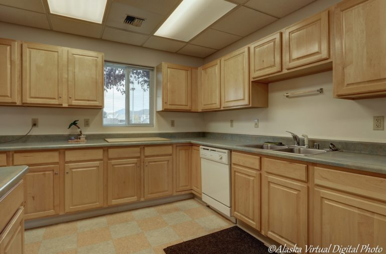 Photo of kitchen with wooden cabinets and tile floor