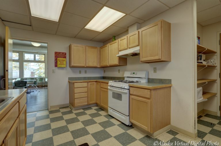 Community center kitchen with checkered teal and white floor, wood cabinets, and matching teal countertops