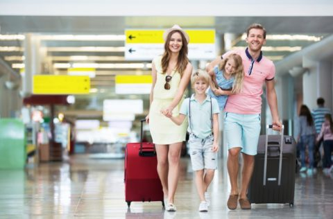 Happy family of four with suitcases in the airport