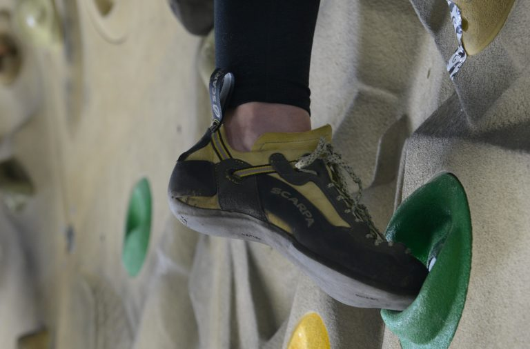 Close up of a climber's shoe as he ascends an indoor climbing wall