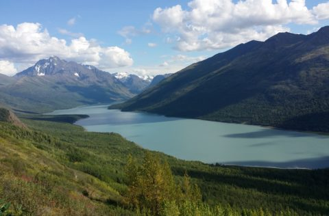 A clear summer view of a long grey-blue lake between two green mountain peaks. This is Alaska's Eklutna Lake