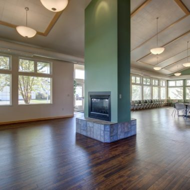 Inside the Community Center at Moose Crossing there are mint green walls, dark hardwood floors, a fireplace, a TV & more