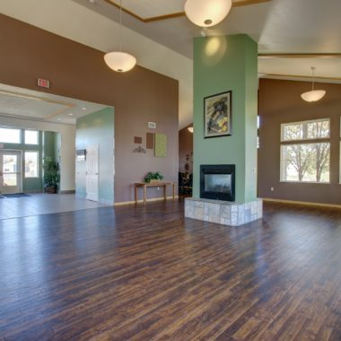 Inside the Community Center at Moose Crossing there are mauve & mint green walls, dark hardwood floors, a fireplace, a TV & more