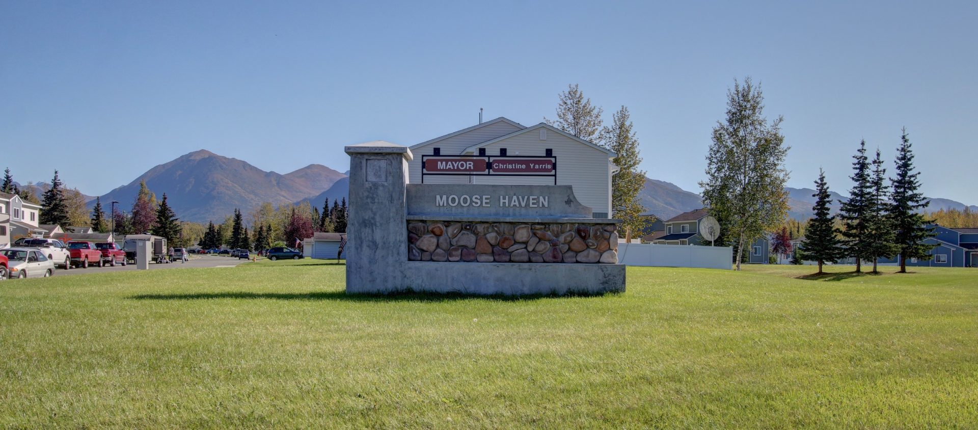 A stone & concrete sign in a green field marks the entrance to JBER's Moose Haven neighborhood