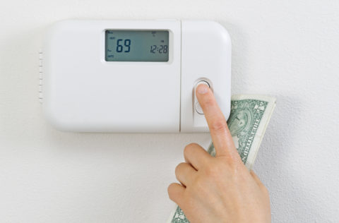 Close up of female hand adjusting home heating thermostat with money in hand.