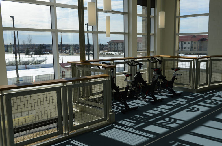 Three stationary bikes look out to a parking lot at an indoor gym