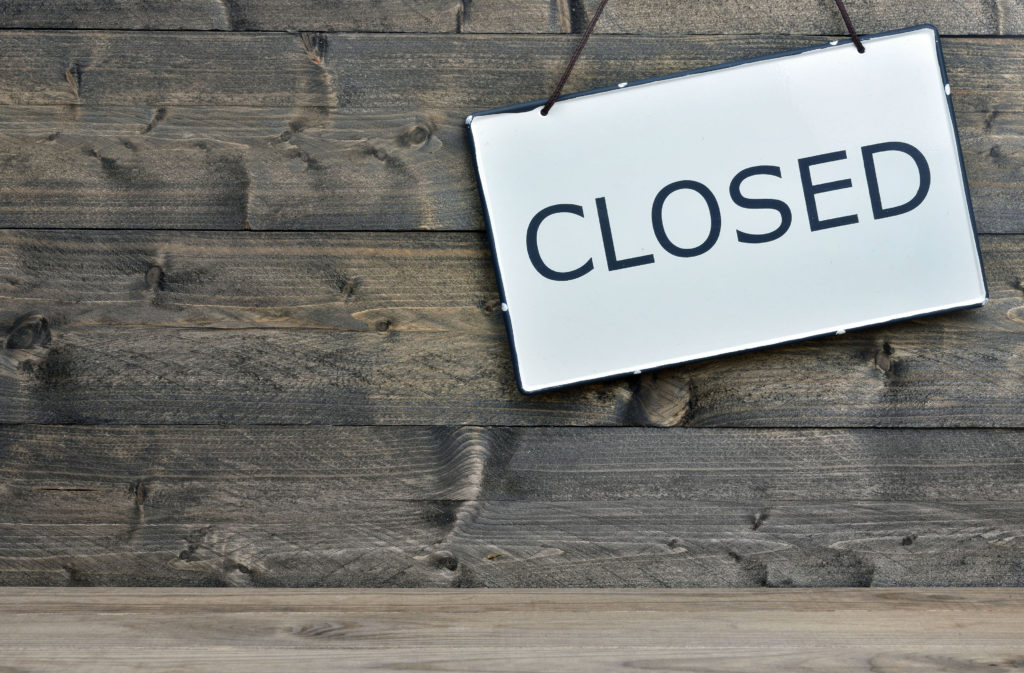 closed message on white sign with wooden background