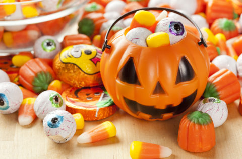Photo of candy scattered around a plastic pumpkin.