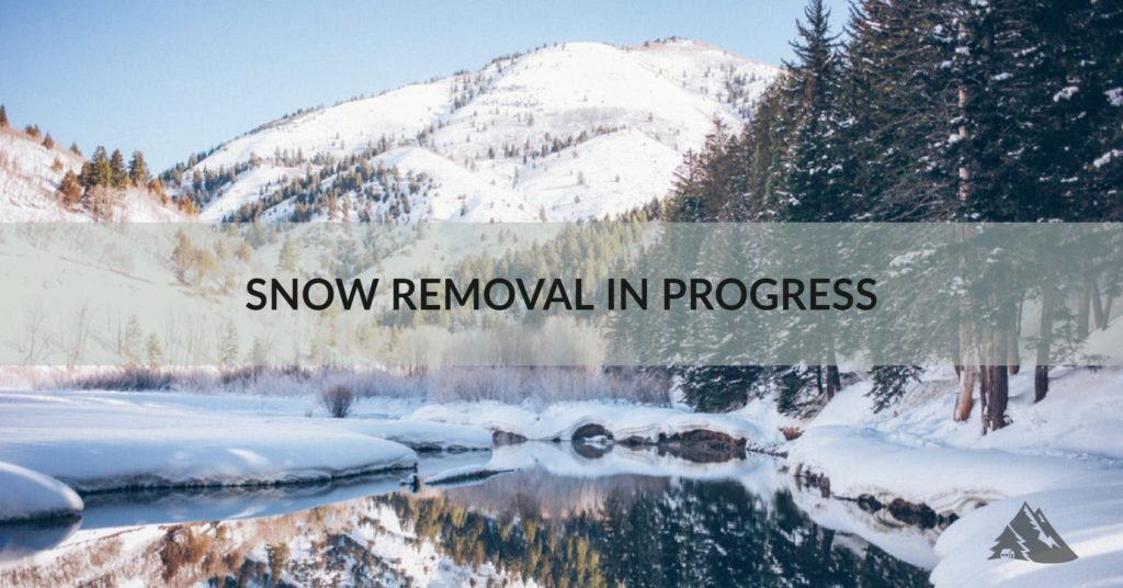 Image of mountains with text stating that snow removal is in progress