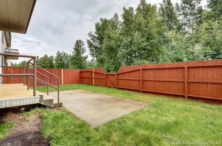 Photo of back yard with red fence