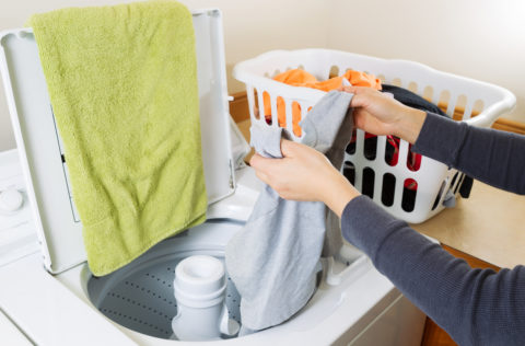 Horizontal photo female hands putting dirty laundry into washing machine