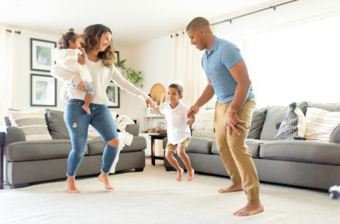 family in living room jumping