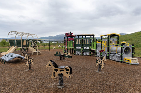Western themed playground with bouncy horses, wagon, and train. Chugach Mountains in background